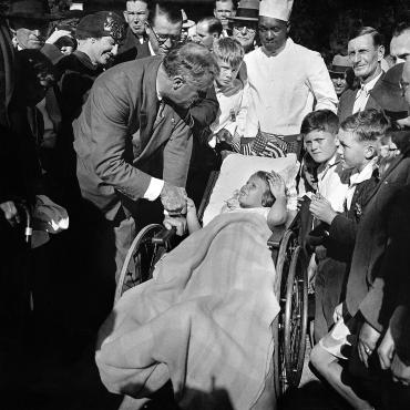 The New York governor shakes the hand of Mary Frances Jasper, a patient at the polio treatment center in Warm Springs, Ga.